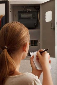 Woman holding a checklist checking her home's electrical system