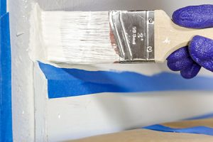 Paintbrush painting walls with mold preventing paint