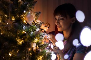 woman hanging ornaments on a Christmas tree